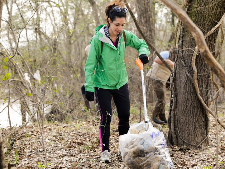 Caitlin Russo picks up trash along the banks of the