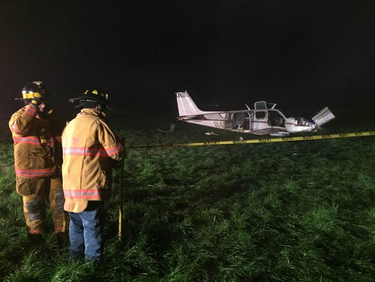 Firefighters place police tape around a single-engine
