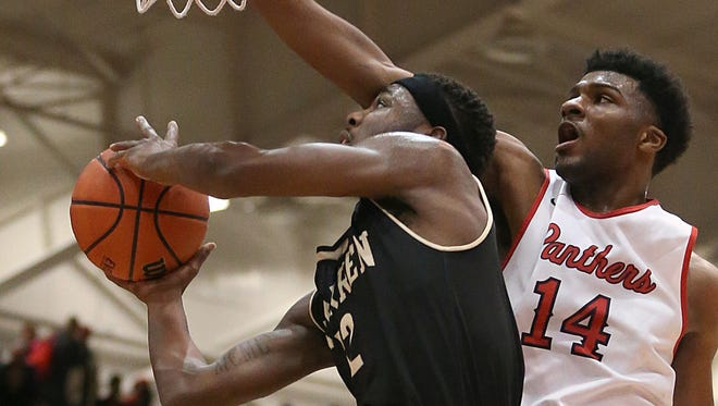 North Central Panthers Emmanuel Little (14) blocks a shot by Warren Central Warriors Trequan Spivey (12)  during second half action between Warren Central and North Central in Marion County boys semifinals, at Southport High School, Indianapolis, Friday, Jan. 13, 2017. North Central won, 69-65.