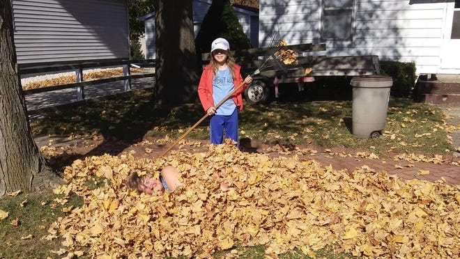 Pictured are Elisa (with the rake) and her grandma Theresa Miller. If you're unable to see Miller, look closely in the leaves. How fun does that look?