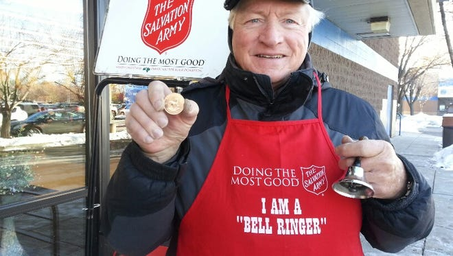 Salvation Army bell ringer Robert Thompson holds up the gold coin that was dropped in his kettle at Hobby Lobby Saturday.