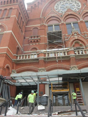 Workers clear debris from in front of Music hall as a major repair and renovationof the building is underway.