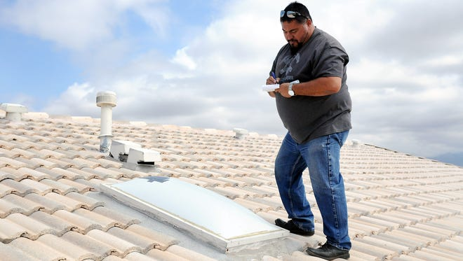 Luis Garcia, with Garcia Roofing, writes down measurements of a skylight on Monday that was damaged by SaturdayÕs hailstorm at a home on El Segundo Trail.