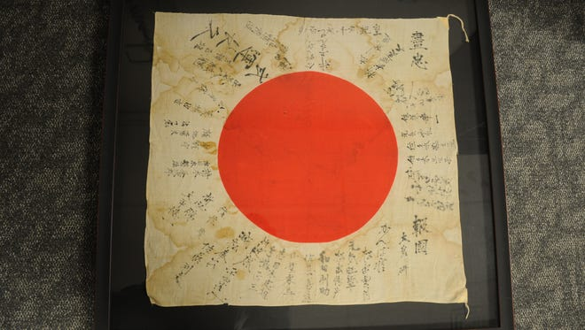 """Fitted in a frame for preservation, Dr. Jessica Jordan is both haunted and intrigued by the tattered Japanese war flag in her office. The worn national flag covered in personal handwritten messages dates to World War II. The flags are known in Japan as a hinomaru yosegaki and in English as """"good luck flags"""". (Photo Credit: AFCLC Outreach, Seth Maggard)"""