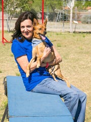 Volunteer Andrea Oatis takes out a dog for exercise at the Arizona Humane Society in Phoenix on Monday, April 7, 2014.