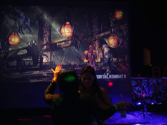 """BART is a new bar located in Cathedral City that has a hipster them including retro video games, colorful art and art. In this photo a screen shot of """"Mortal Kombat"""" is shown as two women dance on the dance floor."""