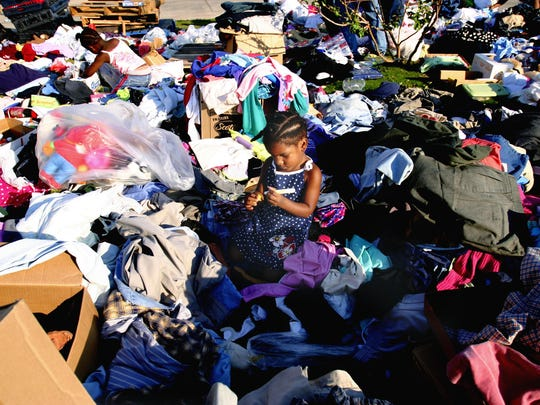 Jamiyah Nelson, 3, plays among a pile of donated clothing at the American Red Cross shelter in Hattiesburg while her mother gathers needed supplies on Sept. 3, 2005.
