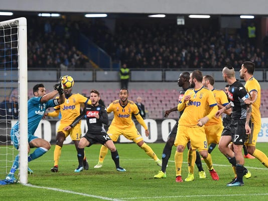 FILE - In this Dec. 1, 2017 file photo, Juventus goalkeeper Gianluigi Buffon, left, saves on Napoli's attack during the Italian Serie A soccer match between Napoli and Juventus at the San Paolo stadium in Naples, Italy. The contrasts between six-time defending champion Juventus and Italian league leader Napoli are endless, yet the difference in the standings is just one point, and has been for more than two months, making Serie A by far the most competitive of Europe's five major league leagues this season. (Ciro Fusco/ANSA via AP, file)