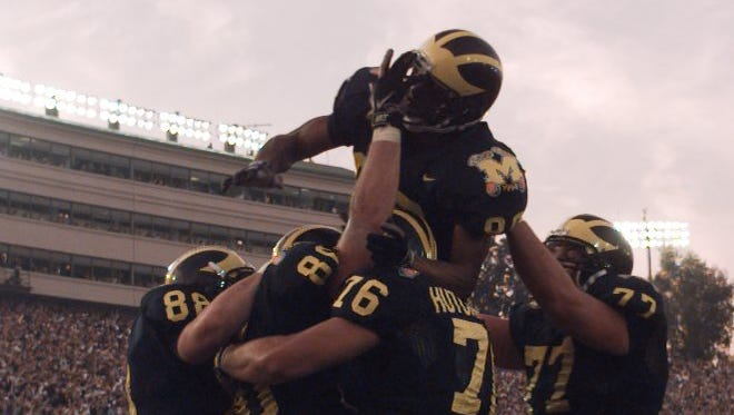 Michigan receiver Tai Streets jumps onto his teammates as the Michigan players celebrate after a score against Washington State during the Rose Bowl on Jan. 1, 1998.