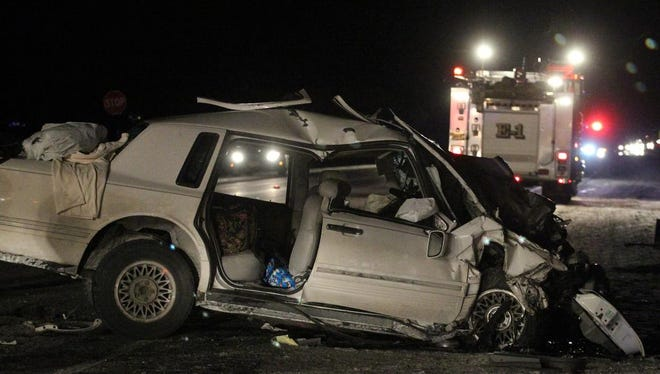 A white sedan sits on Highway 13 north of Marshfield, Wednesday, February 4, 2015. It was one of two vehicles involved in a fatal crash.