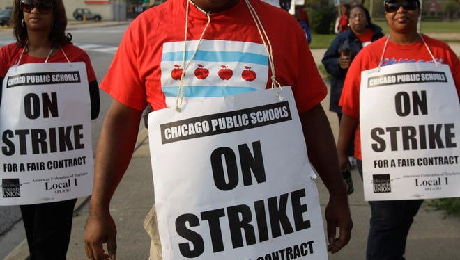 A group of teachers picket outside Morgan Park High School in Chicago, Monday, Sept. 17, 2012. Teachers in Chicago are threatening to go on strike again early next year if a new contract deal is not completed soon.