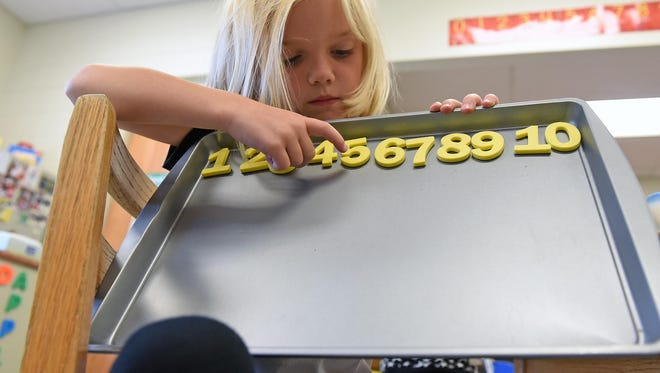 Kindergartner Sabrina Thompson shows her number chart at Milanesi Elementary School in Buena on Tuesday.
