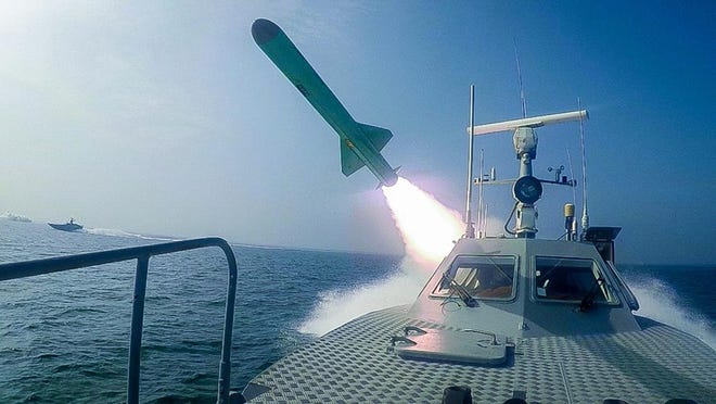 """In this photo released Tuesday, July 28, 2020, by Sepahnews, a Revolutionary Guard's speed boat fires a missile during a military exercise. Iran's paramilitary Revolutionary Guard has fired a missile from a helicopter targeting the mock-up aircraft carrier in the strategic Strait of Hormuz. That's according to footage aired on state television on Tuesday. Iranian commandos also fast-roped down from a helicopter onto the replica in the footage from the exercise called """"Great Prophet 14."""" The drill appears aimed at threatening the U.S. amid tensions between Tehran and Washington."""