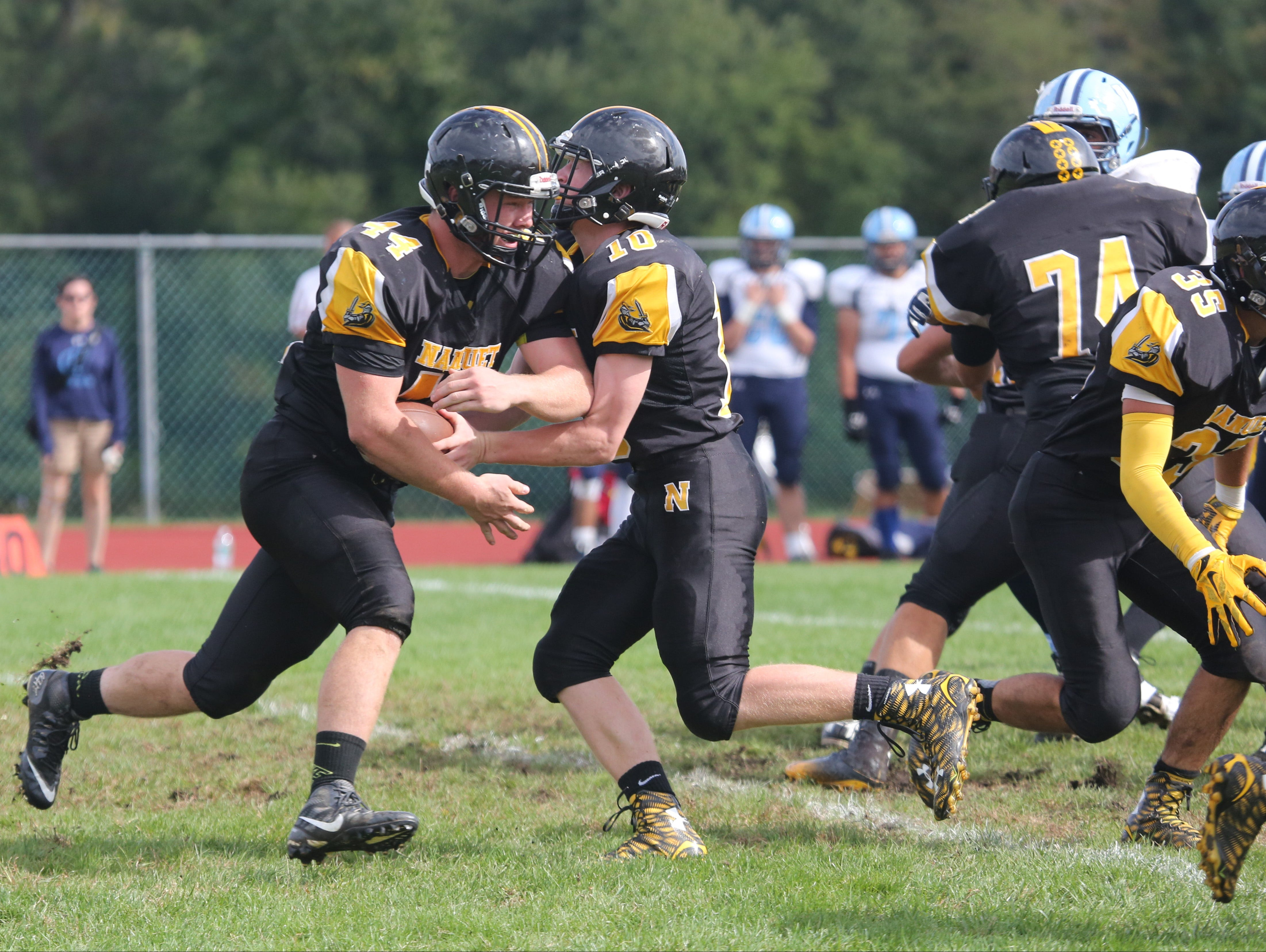 Nanuet quarterback Thomas Fay hands off to Connor Breit during action in the Nanuet vs. Westlake football game in Nanuet, Sept. 26, 2015.