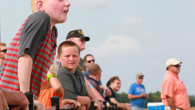 Logan Moore of Anderson props himself higher on the fence watching Gary Ward practice stunts with his plane at the Anderson Regional Airport before the 2015 airshow.