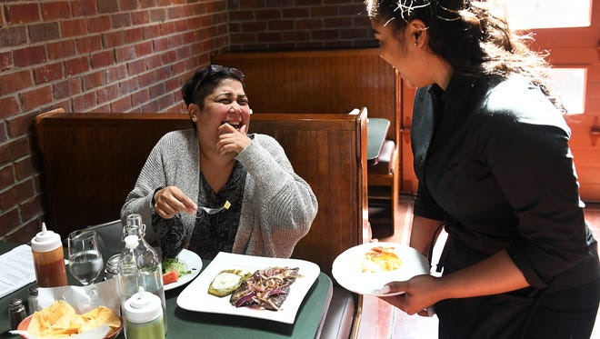Patron Maria Aloyo of Allen Park chats with server Heylee Canales after lunch is served at La Noria Bistro.