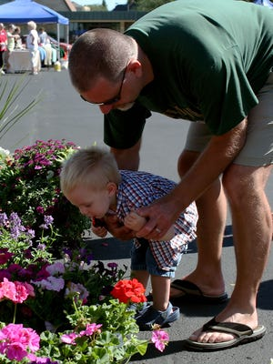 John-David Miller was drawn to the fragrant flowers shopping the Farmers Market with grandpa, Tom Winkels.