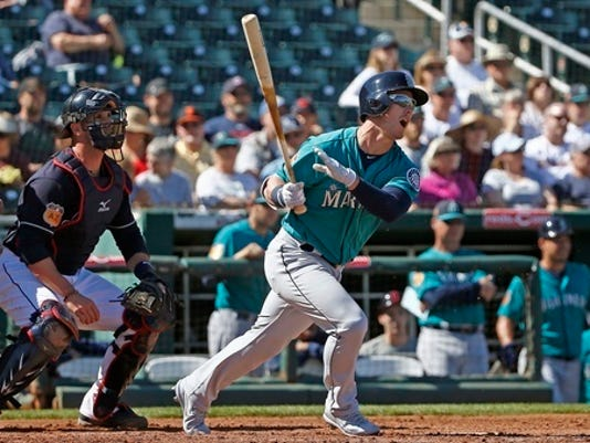 FILE - In this March 1, 2017, file photo, Seattle Mariners' Boog Powell, right, follows through on his swing as Cleveland Indians catcher Yan Gomes, left, looks on during the third inning of a spring training baseball game in Goodyear, Ariz. For the record, Mariners newcomer Powell made his major league debut Saturday, April 29, 2017. Just do no look for any stats to prove it. (AP Photo/Ross D. Franklin, File)