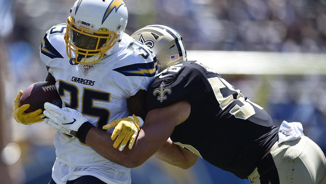 Chargers rusher Troymaine Pope is hauled down by Saints linebacker Kaden Elliss during their preseason game. The Saints won, 19-17.