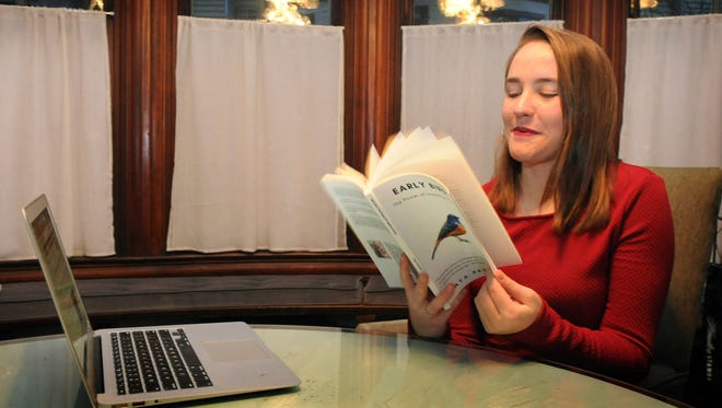 """Maya Peterson, 15, flips through the new book she's written about investing called """"Early Bird: The Power of Investing Young,"""" in her parents St. Paul, Minn. home on Wednesday, Nov. 29, 2017. Peterson wrote, designed, formatted and published the book on her own. (Ginger Pinson/St. Paul Pioneer Press via AP)"""