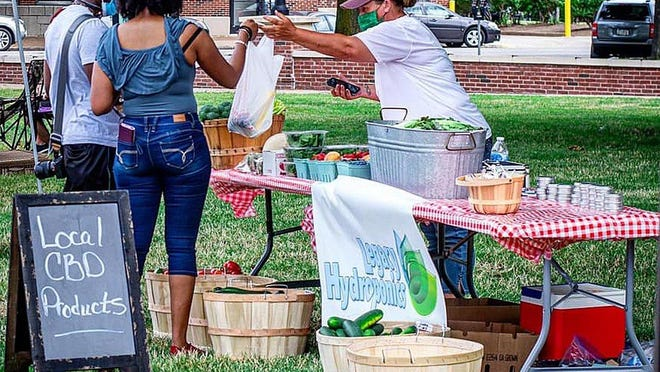 A couple buys produce from Legacy Hydroponics LLC in Waterford at the farmers market in Perry Square, which quietly launched July 19.