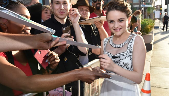"""Actress Joey King signs autographs as she arrives at the Los Angeles premiere of """"Wish I Was Here"""" at the Directors Guild of America Theater in 2014."""