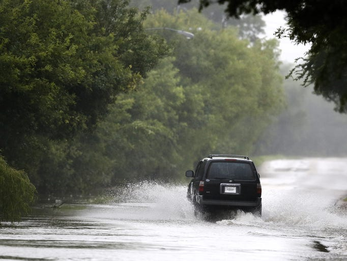 A driver navigates his way through flood waters after