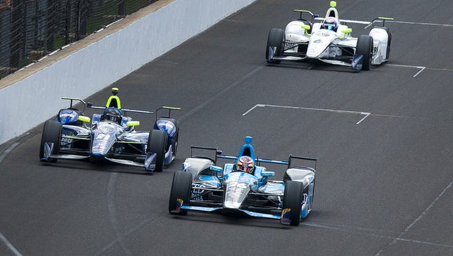 IndyCar driver Carlos Munoz (26) passes IndyCar driver Josef Newgarden (21) late in the race during the 100th running of the Indianapolis 500, Sunday, May 29, 2016, in Speedway, Ind.