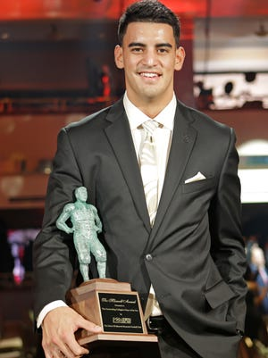 Oregon quarterback Marcus Mariota stands with his trophy after being awarded the Maxwell Award as the college player of the year at the College Football Awards, Thursday, Dec. 11, 2014, in Lake Buena Vista, Fla. (AP Photo/John Raoux)