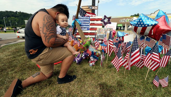 Bryan Thaboua kneels with his 8-month-old son, Cooper Thaboua, on July 20, 2015, beside the Lee Highway memorial to the five servicemen slain last week at a U.S. Navy site in  Chattanooga, Tenn.