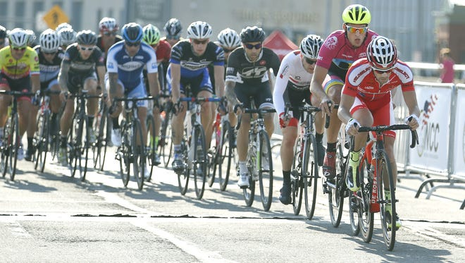 Cyclists race through the downtown Rochester streets in the men's professional race at the 2015 Twilight Criterium.