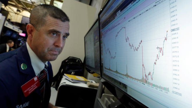 Trader Stephen Guilfoyle looks at a chart of the day's trading on a monitor on the floor of the New York Stock Exchange.
