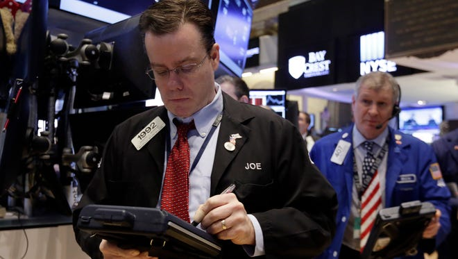 Trader Joseph Murray (left) works on the floor of the New York Stock Exchange, Friday, March 6, 2015. Stocks opened lower on Friday as another strong U.S. jobs report raised the likelihood that the Federal Reserve would start to raise interest rates later this year.