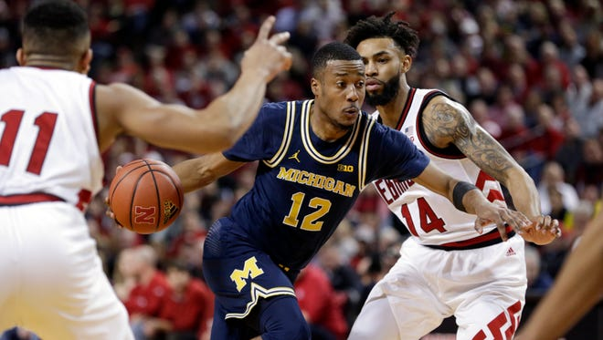 Michigan's Muhammad-Ali Abdur-Rahkman drives to the basket between Nebraska's Evan Taylor (11) and Isaac Copeland (14) during the first half in Lincoln, Neb., Thursday, Jan. 18, 2018.