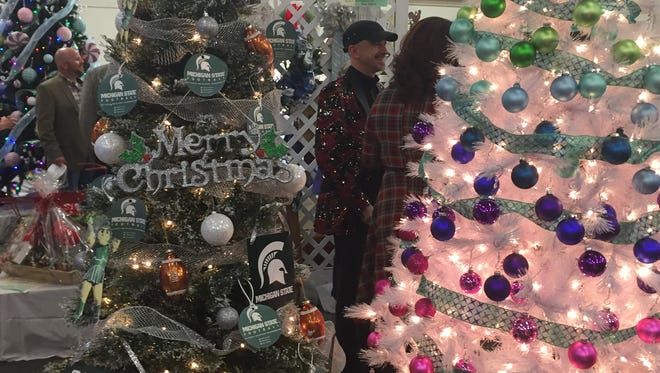 Bidders admire a variety of decorated trees during the annual Festival of Trees. The auction is a fundraiser for the  Zanesville-Muskingum County Chamber of Commerce.