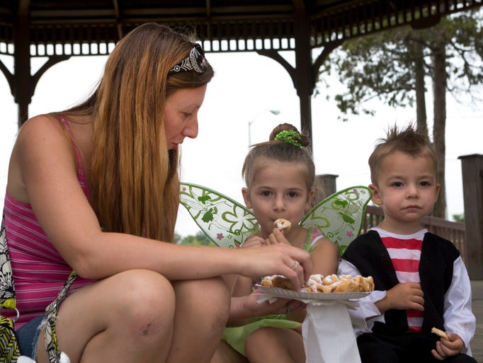Melissa  Harris of South Toms River shares a funnel cake with her children Grace, 5, who is dressed as Tinkderbell and son Damian, 2, dressed as a pirate as they wait for the start of the Valhallas Pirates show at the Toms River Wooden Boat Show in Huddy Park Toms River, NJ on July 19, 2014. Peter Ackerman / Staff Photographer