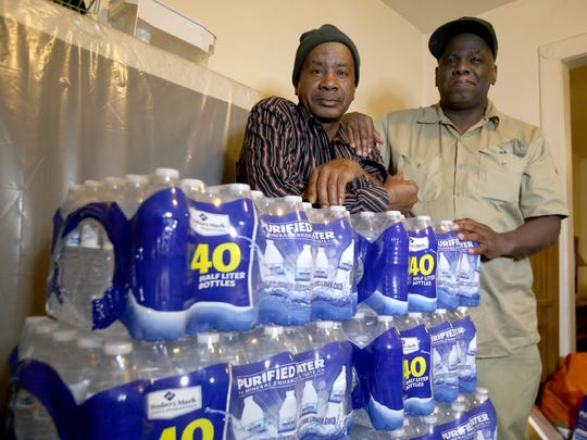 (L to R) Brothers James Thompson, 57, and Jimmy Thompson, 58, of Flint in their dining room with stacks of bottled water.