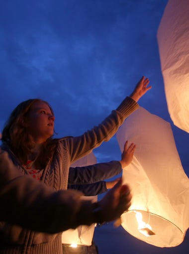 Friends and classmates of 2009 Tappan Zee High School graduate Melissa Dimataris release sky lanterns in her memory during a ceremony at the Piermont Pier April 22, 2014. Dimataris battled leukemia and died at age 22 in October 2013.
