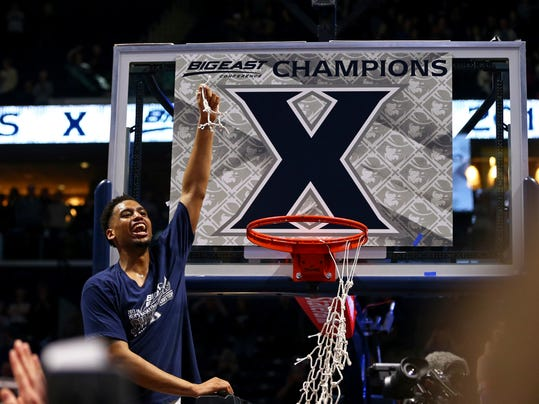 Xavier's Trevon Bluiett holds up a piece of net after clinching at least a share of its first Big East championship after an NCAA college basketball game against Providence, Wednesday, Feb. 28, 2018, in Cincinnati. Xavier won 84-74. (AP Photo/Aaron Doster)