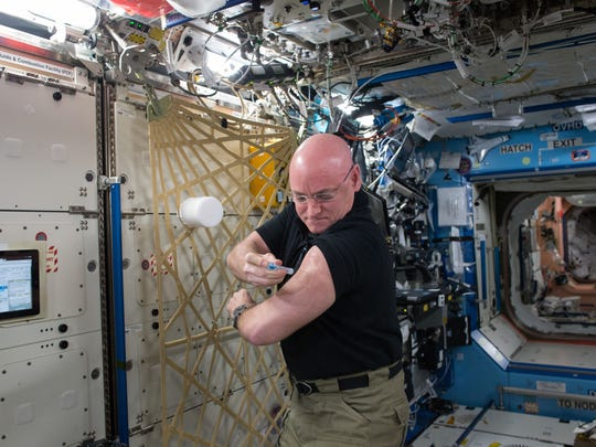In this Sept. 24, 2015 photo made available by NASA, astronaut Scott Kelly gives himself a flu shot aboard the International Space Station for an ongoing study on the human immune system. The vaccination is part of NASA's Twins Study, a compilation of multiple investigations that take advantage of a unique opportunity to study identical twin astronauts Scott and Mark Kelly, while Scott spends a year aboard the station and Mark remains on Earth.