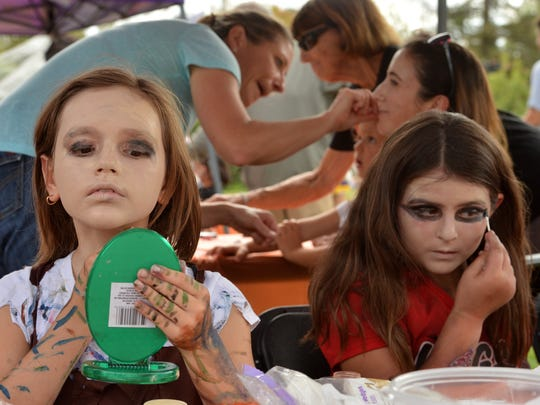 Taya Svetlov, left, and Sophia Sarni, both Girl Scouts in Calabasas, do their makeup before attempting to break a world record in Thrill the World synchronized zombie dance Saturday at California Lutheran University.