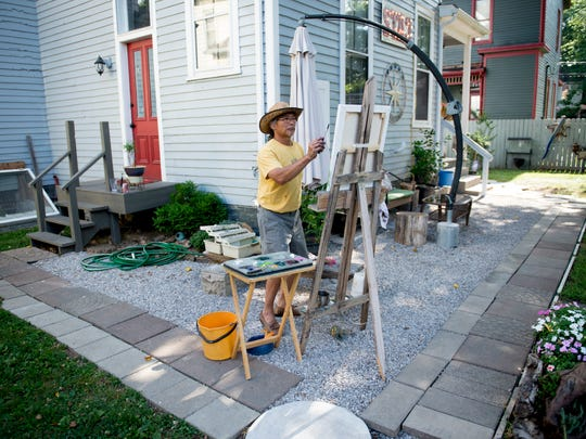 Ted Nguyen works on a painting behind the StaC Art Gallery at 416 Washington Ave. in Evansville Tuesday evening. Nguyen is the artist-in-residence of the gallery which will hold its grand opening from 5-10 p.m. Friday.