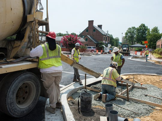 A construction crew work to pour concrete on a sidewalk at the corner of Poplar Hill Avenue and East Main Street in Salisbury on Friday, July 21, 2017.