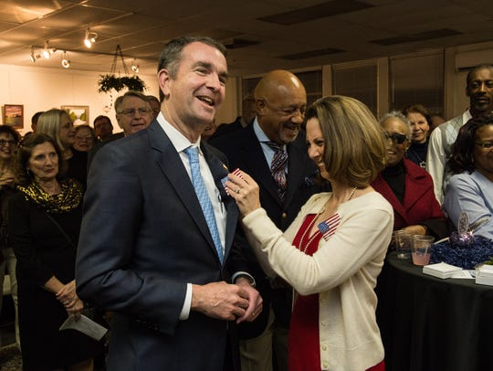 Virginia's first lady Pamela Northam pins a paper mache