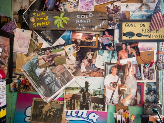 A section of the wall just inside the front door of Little Jim Bait & Tackle displays photos of friends and customers of the shop, as seen May 30, 2018, in Fort Pierce. Owners Richard King — seen in the photo at bottom holding a lobster caught during mini-season — and his wife, Rita King, are retiring after their run of the business, which originally opened in the same building in 1944.