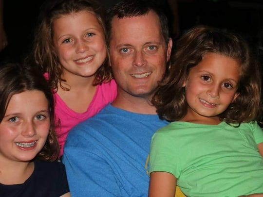 Doug Alongi pictured with his daughters, from left