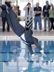 St. Norbert President Tom Kunkel dives into the new swimming pool Friday after the dedication ceremony for the Mulva Family Fitness and Sports Center at St. Norbert College. The facility has undergone a $26 million renovation and expansion which includes a new swimming pool and a fitness center.