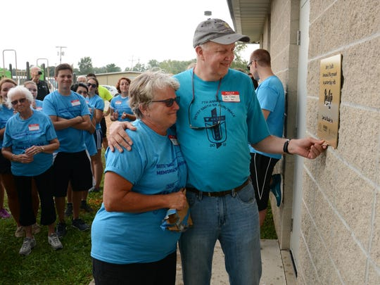 Dan and Jeanie Smith look at the plaque near the site of the playground built in memory of their daughter.