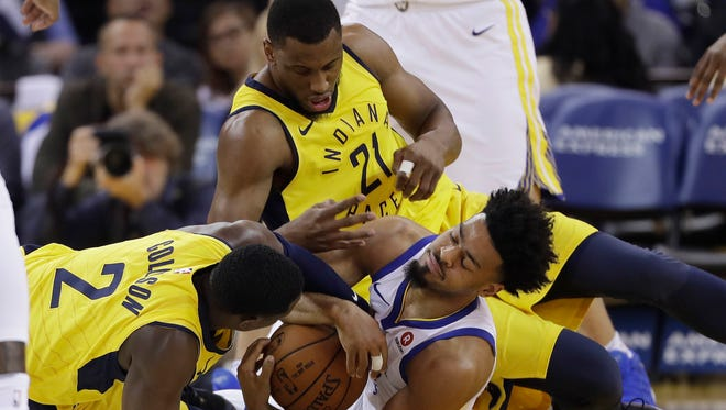Golden State Warriors' Quinn Cook, bottom, right, scramble for a loose ball against Indiana Pacers' Darren Collison (2) and Thaddeus Young (21) during the first half of an NBA basketball game Tuesday, March 27, 2018, in Oakland, Calif.