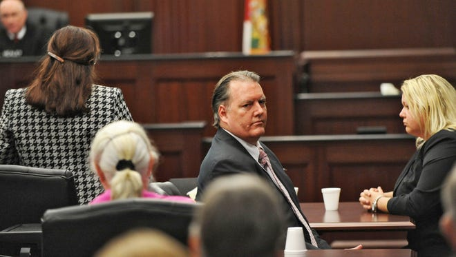 Michael Dunn, center, looks back at his parents after the verdict of guilty in his retrial Wednesday, Oct. 1, 2014, the Duval County Courthouse in Jacksonville, Fla.,  jury found Dunn guilty of first-degree murder in his retrial on murder charges for the shooting death of 17-year old Jordan Davis in a dispute over loud music at at Jacksonville gas station in November of 2012.